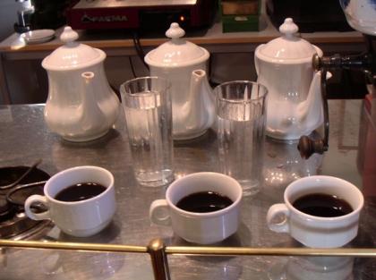 Kaffee aus der Karlsbader Kanne wird mit einem Glas Wasser zum Servieren vorbereitet.