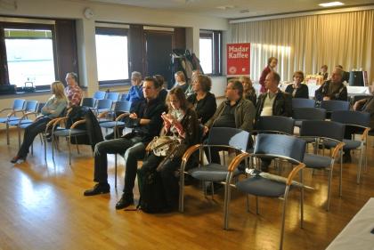 Die ersten Zuhörer warten schon gespannt auf den Beginn des Vortrags.