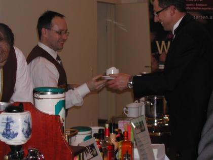 Chef-Dipl.Somm. Heschl übergibt einem Ballbesucher einen Kapuziner, zubereitet in der Karlsbaderkanne, serviert mit einer Schlagobershaube.