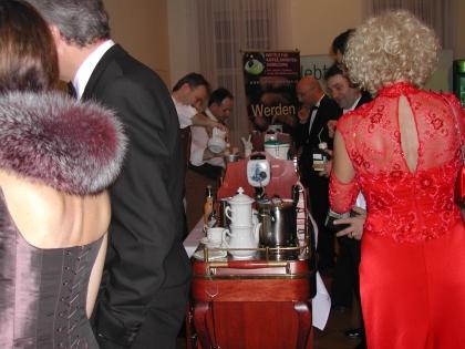 Damen und Herren in prachtvollen Roben drängen sich um die Kaffeewagen.